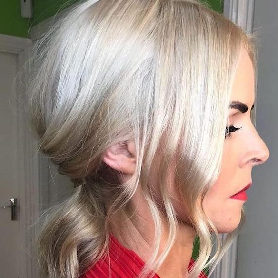 Side profile of woman with icy blonde hair styled in a low ponytail, created using Wella Professionals.