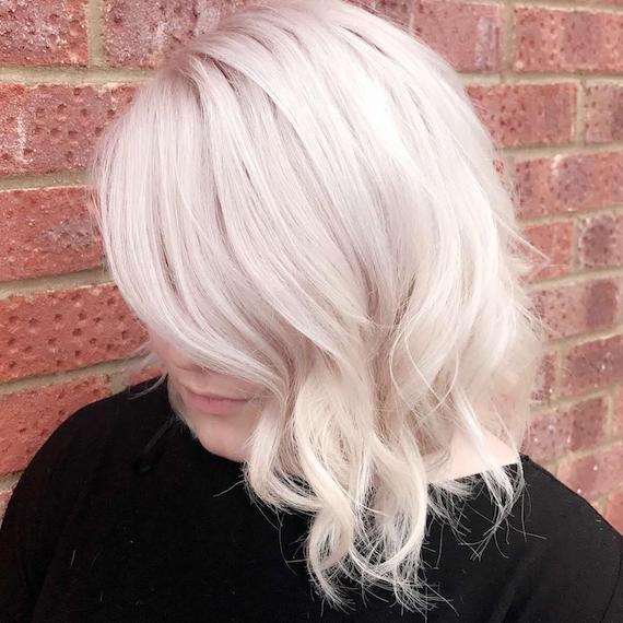 Ice blonde, side-swept bob with loose curls, created using Wella Professionals