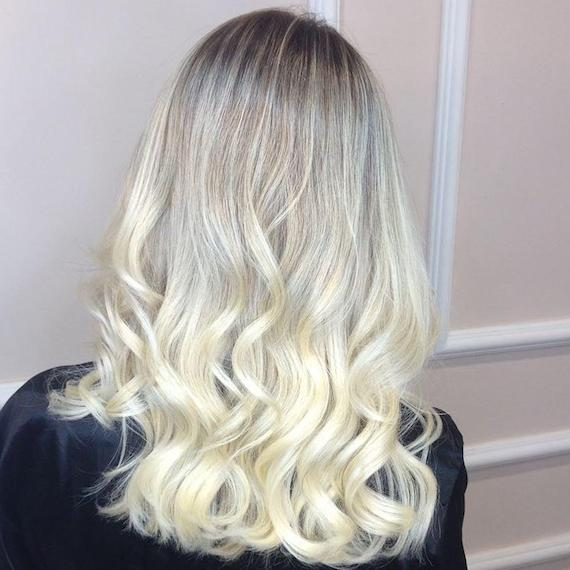 Woman with ice blonde, loosely-curled hair and dark roots, created using Wella Professionals