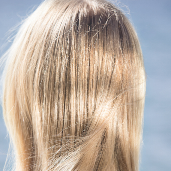 Woman with windswept, satin blonde hair, created using Wella Professionals