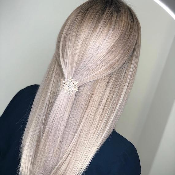 Back of a women's head with long, straight, ice blonde hair and a snowflake clip