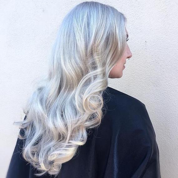 Side-on photo of woman with long, curly ice blonde hair, created using Wella Professionals