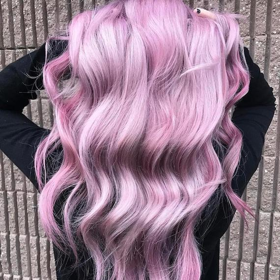 Photo showing the back of a woman's head as she swishes her long, wavy, metallic pink hair, created using Wella Professionals