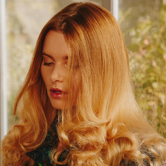 Close-up photo of model gazing downwards. Her golden blonde hair is styled in loose, lightly-tousled waves, by Wella Professionals