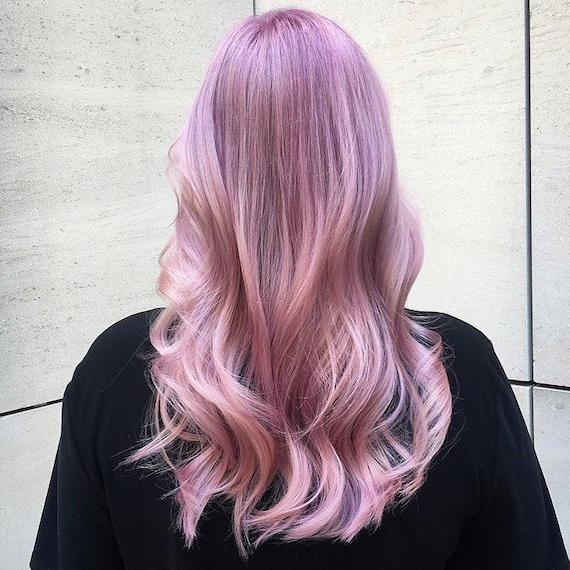 Woman with long, wavy, metallic pink hair styled in loose waves, created by Wella Professionals