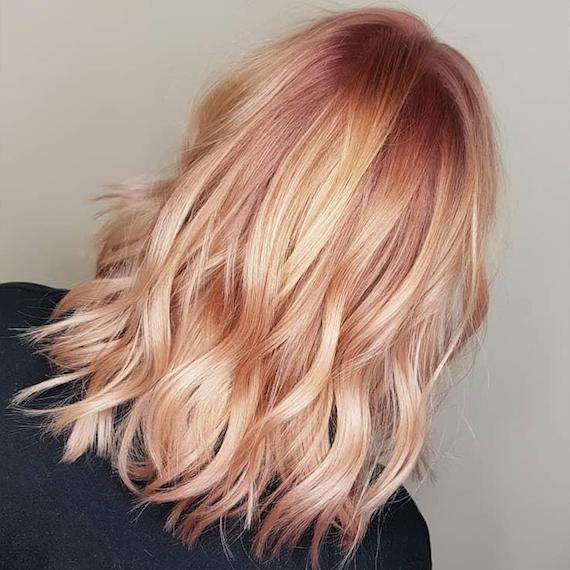 Back of woman's head showing wavy, peach and pink hair color, created using Wella Professionals
