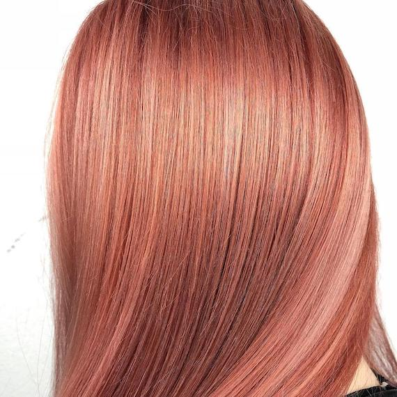 Back of woman's head showing straight, sleek, peach hair, created using Wella Professionals