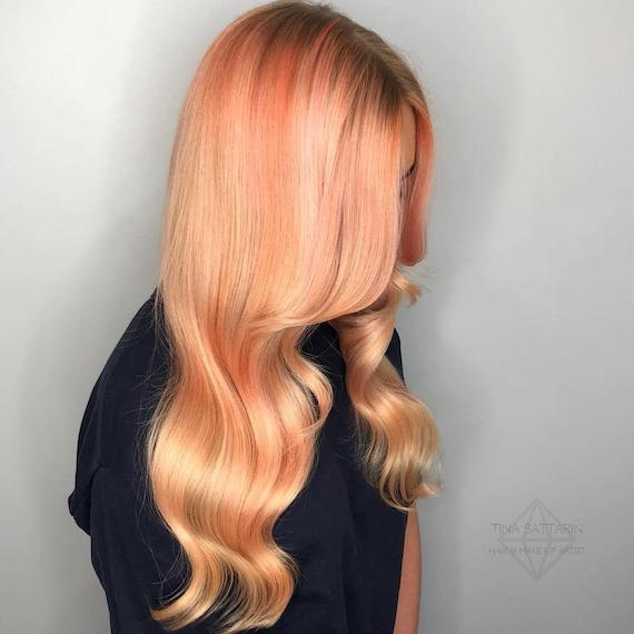 Woman with wavy, peach and orange hair color, created using Wella Professionals