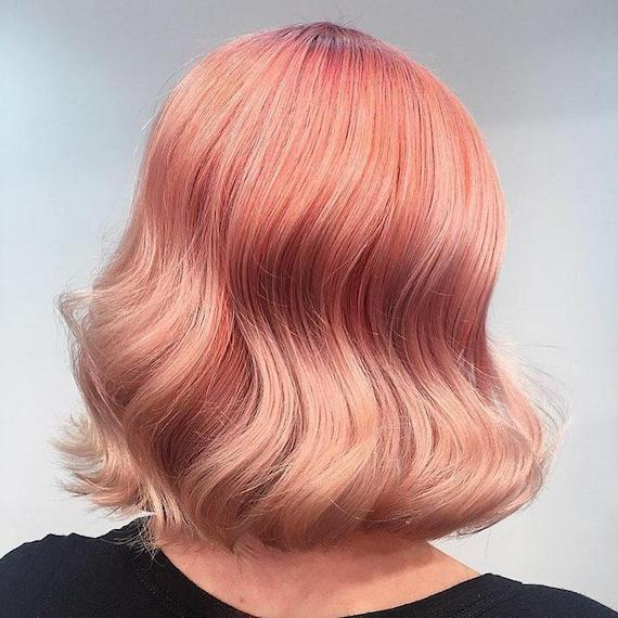 Back of woman's head showing wavy, pinky-peach hair color, created using Wella Professionals