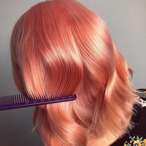 Back of woman's head with a comb running through wavy, peach hair color, created using Wella Professionals