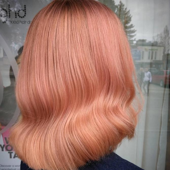 Back of woman's head showing wavy, peach hair color, created using Wella Professionals