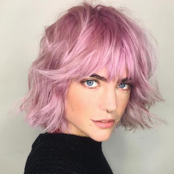 Front-on photo of woman with tousled bob and fringe in a metallic pink shade, created using Wella Professionals