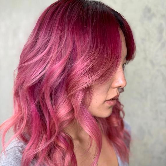 Model with long, pink hair styled in loose curls, created using Wella Professionals