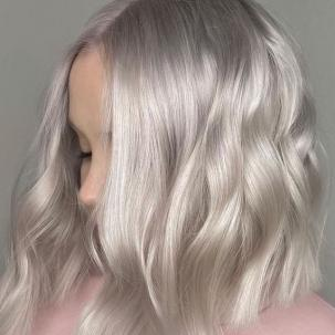 Side profile of woman with short, wavy, ice blonde hair, created using Wella Professionals.