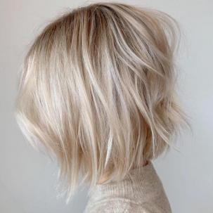 Side profile of woman with short baby blonde bob, created using Wella Professionals.