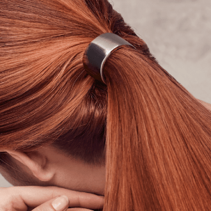 Photo of the back of a woman's head, with glossy red hair tied in a low ponytail.