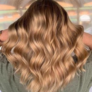 Back of woman's head with long, wavy hair and honey blonde foilyage, created using Wella Professionals.