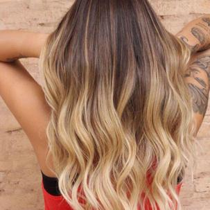 Woman with long golden blonde hair wit dark roots, styled with loose waves