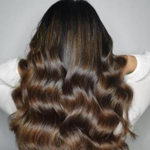 Back of woman's head with long, loosely curled, mocha brown hair, created using Wella Professionals.