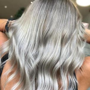 Back of woman's head with long, wavy, gray blonde hair, created using Wella Professionals.