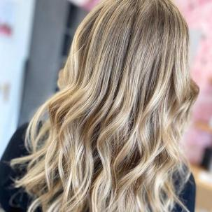 Back of woman's head with tousled, mid-length beige blonde hair, created using Wella Professionals.