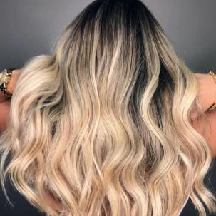 Photo of the back of a woman's head with blonde hair styled in loose waves, created using Wella Professionals.