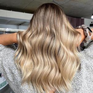 Back of woman's head with long, wavy, ash blonde hair and a shadow root, created using Wella Professionals.