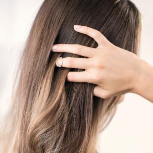 Back of woman's head as she runs her hand through her hair.