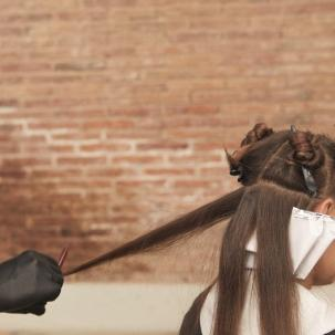 Photo of woman having her brown hair colored in a Wella Professionals salon.
