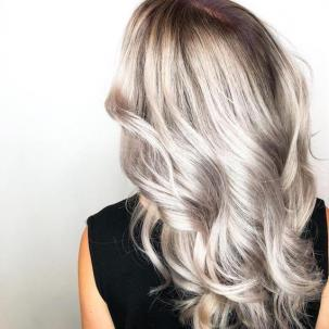 Back of woman's head with long, wavy, silver balayage hair, created using Wella Professionals.