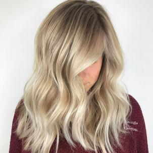 Woman with mid length, beige blonde hair styled with loose waves