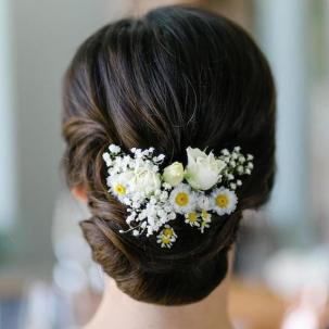 Photo of the back of a woman's head with hair styled in a bridal updo that's decorated with flowers, created using Wella Professionals