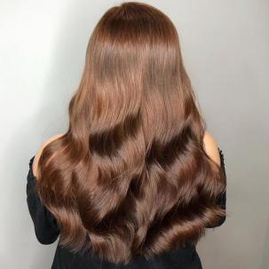 Back of woman's head with long, wavy, brown hair, glossed using Wella Professionals