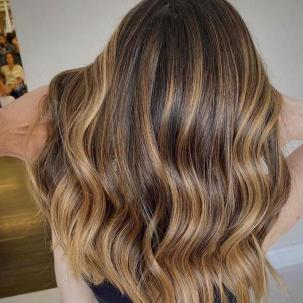Back of woman's head with long, wavy brown hair and warm blonde twilights, created using Wella Professionals.