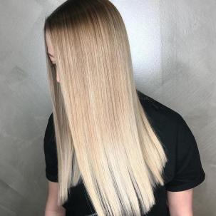 Photo of woman with long, straight, silky, blonde ombre hair, created using Wella Professionals.