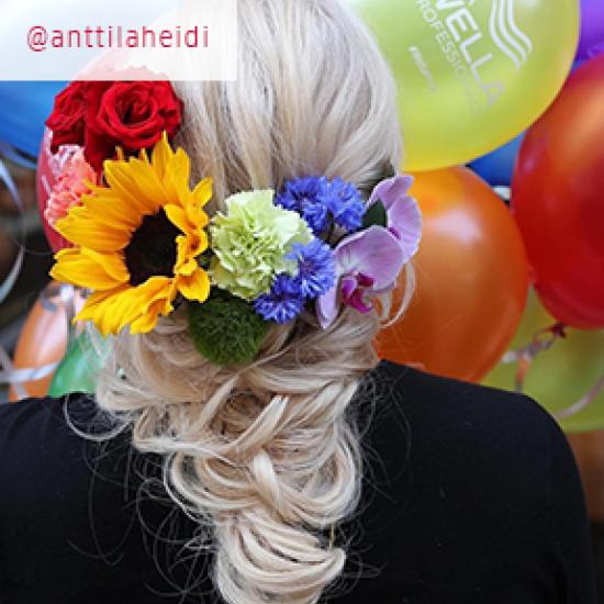 Back of model's head wearing flowers in the colors of the rainbow