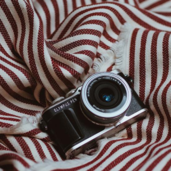 Camera on red and cream striped throw