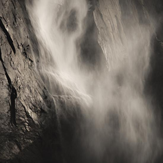 Nebel, der an einer Felswand hinunter fällt