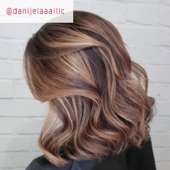 Side profile of woman with with wavy, light brown hair and blonde balayage, created using Wella Professionals.