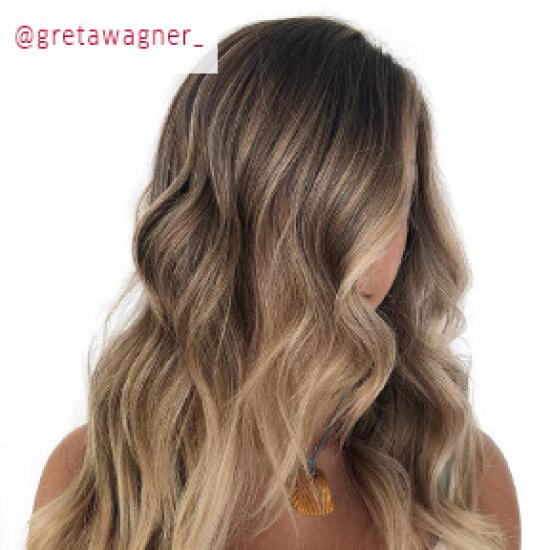 Woman with long, wavy hair and blonde balayage, created using Wella Professionals.