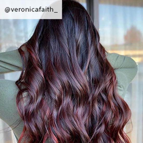Woman with long hair in burgundy balayage styled with loose waves