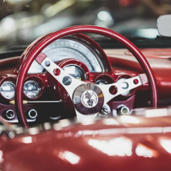 close up of burgundy car wheel and dashboard