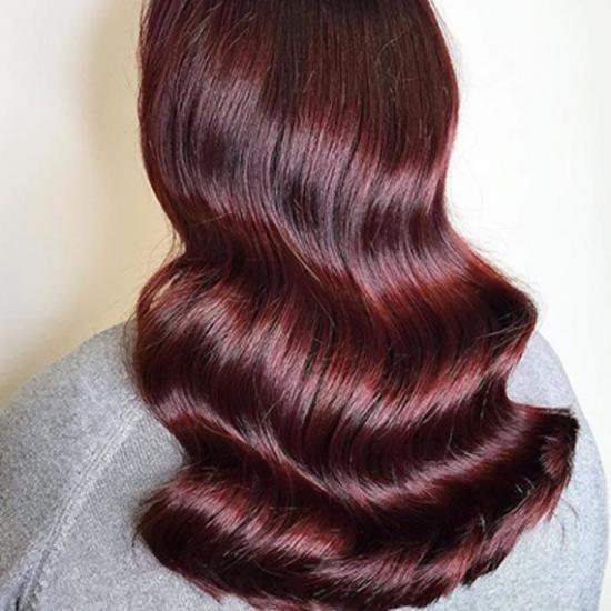 Woman with long, wavy hair in burgundy colour