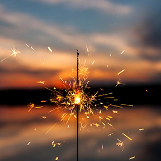 Photo of a sparkler in the foreground and the sunset in the background.