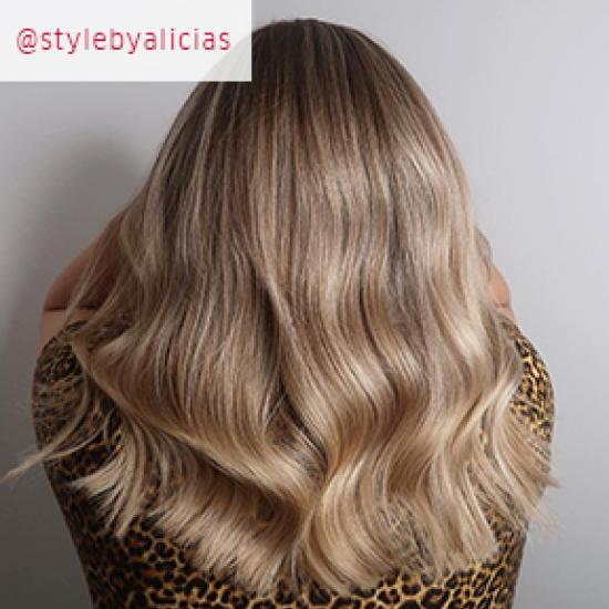 Photo of the back of a woman's head with long, wavy, Powdered blonde hair, created using Wella Professionals.