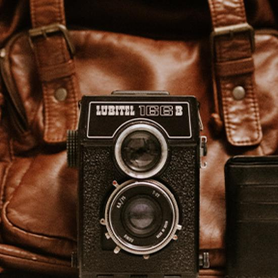 Old photo camera and a brown bag in the background