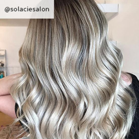 Back of woman's head with long, wavy, dark ash blonde hair, created using Wella Pro-fessionals.