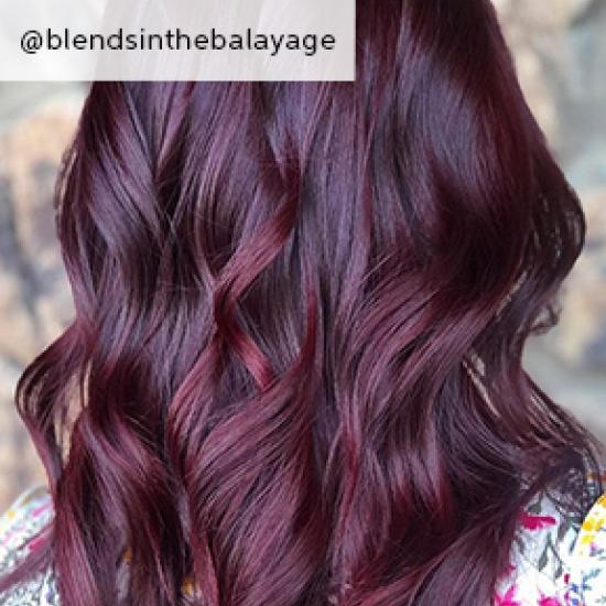 Back of woman's head with loosely tousled, dark purple hair, created using Wella Professionals.