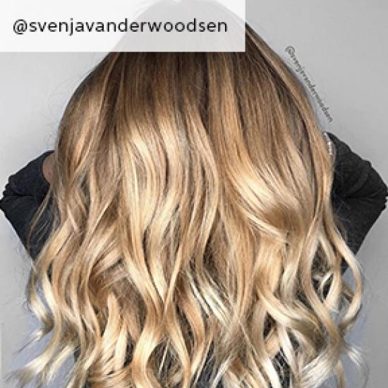 Back of woman's head with long, wavy, golden blonde hair, created using Wella Professionals.
