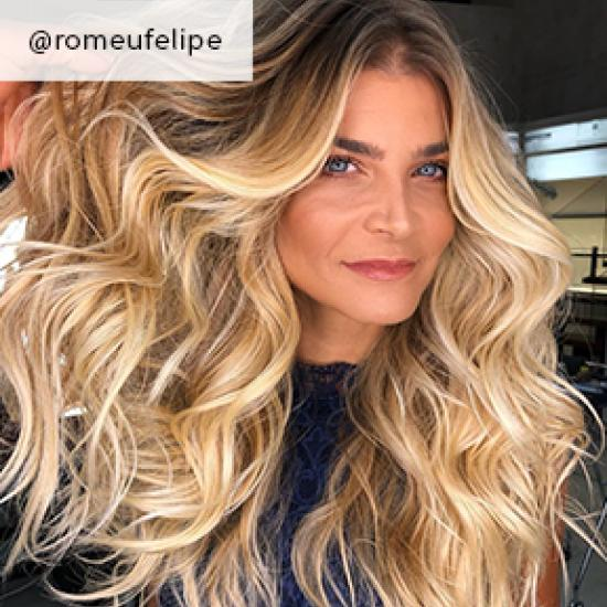 Woman with long, wavy, golden blonde hair, created using Wella Professionals.